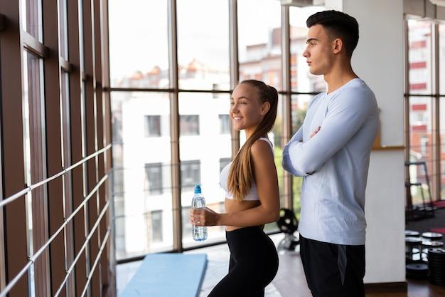 Mann und frau im fitnessstudio mit pause