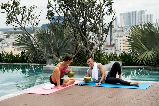Mann und frau im freien nach yoga, das kokoswasser trinkt