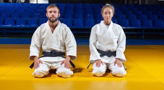 Mann und frau im weißen kimono mit schwarzem gürtel sitzen auf dem boden und meditieren in der sporthalle. orientalische kampfkunst, judo