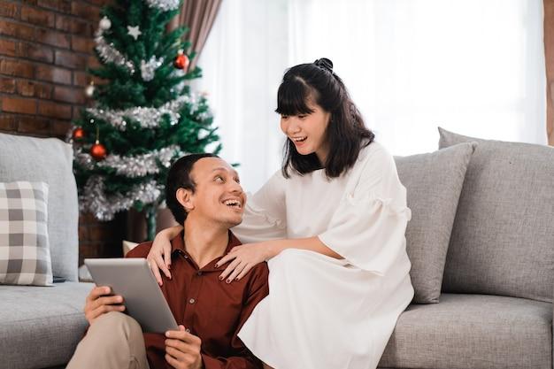 Mann und frau im wohnzimmer zusammen mit tablette pc während des weihnachtstages
