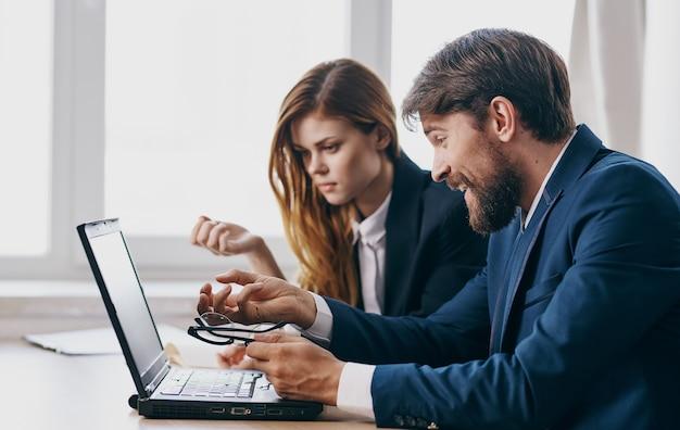 Mann und frau in anzügen arbeiten laptop-finanzmanager. hochwertiges foto