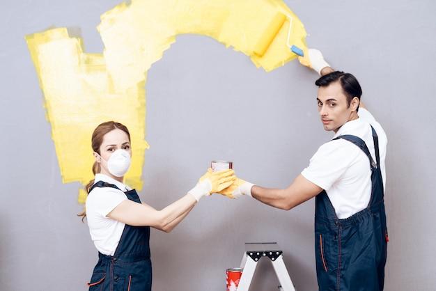 Mann und frau in atemschutzmasken malen graue wand.