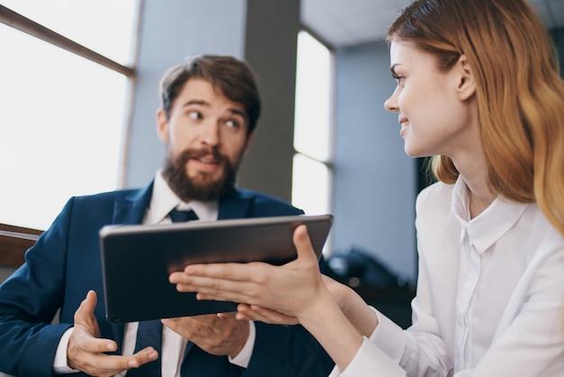 Mann und frau in business-anzügen kommunizieren mit den tablet-managern
