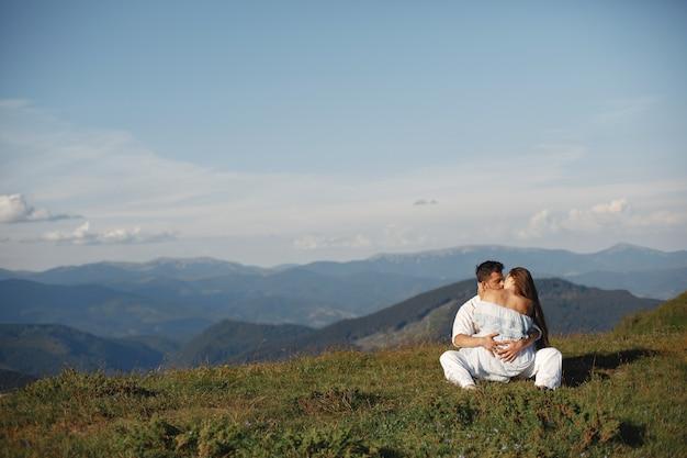 Mann und frau in den bergen. junges paar verliebt in sonnenuntergang. frau in einem blauen kleid.