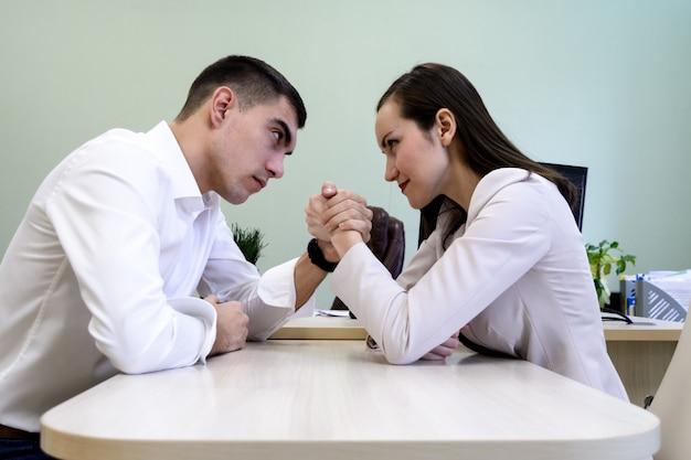 Mann und frau in der bürokleidung, die an hand am schreibtisch im büro ringt