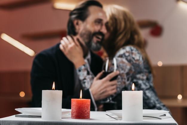 Mann und frau in einem restaurant umarmen an einem tisch weichzeichner