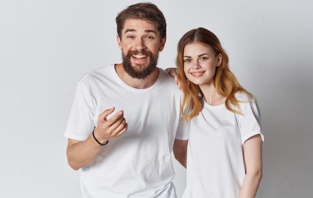 Mann und frau in identischen t-shirts gestikulieren mit den händen beschnittenen blick.