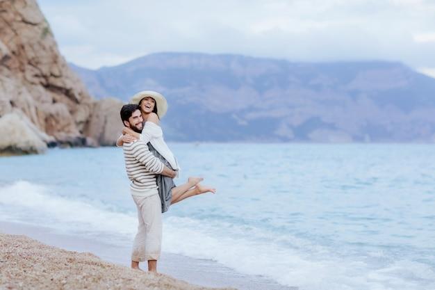 Mann und frau in liebe uddle und küssen am strand