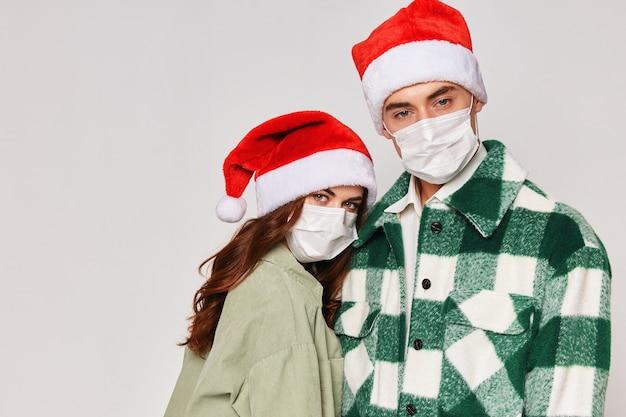 Mann und frau in medizinischen masken weihnachtsmützen umarmungen