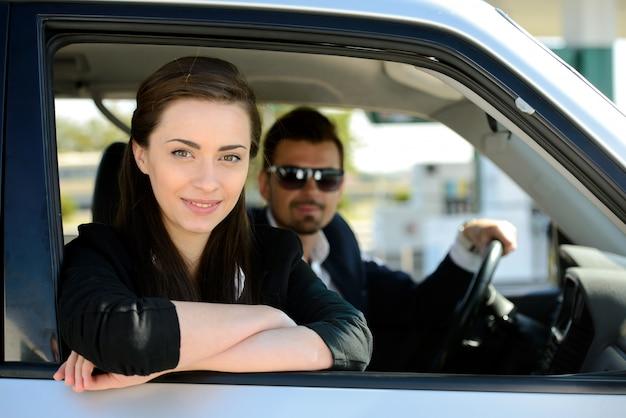 Mann und frau in seinem auto hält an der tankstelle.