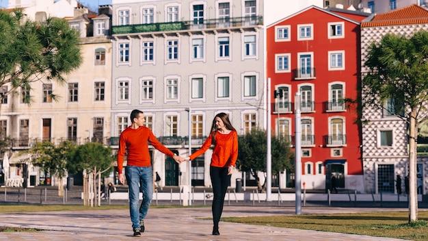 Mann und frau in stilvollen roten pullovern halten hände und schauen sich an. großer platz vor gebäuden.