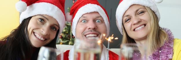 Mann und frau in weihnachtsmann-hüten trinken champagner und halten wunderkerzen in den händen