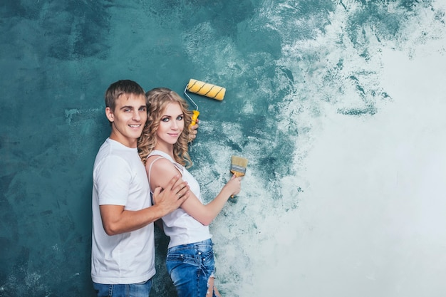 Mann und frau junges und schönes paar, das renovierung in der glücklichen jungen familie des neuen hauses tut