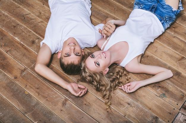Mann und frau junges und schönes paar in weißen hemden, die auf dem holzboden glücklich liegen