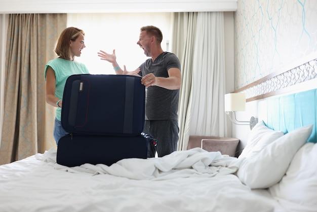 Mann und frau kämpfen im schlafzimmer auf dem bett ist koffer