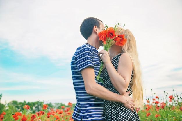 Mann und frau küssen auf dem gebiet der mohnblumen.