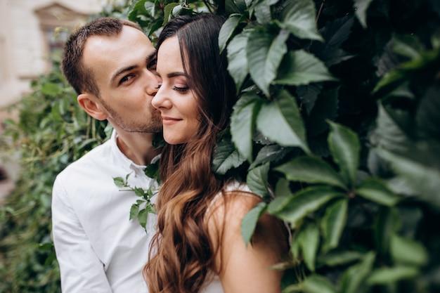 Mann und frau küssen sich zärtlich auf der straße stehen an ihrem hochzeitstag