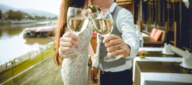 Mann und frau küssen sich zusammen. es gibt hände, die gläser wein im vordergrund halten. fokus an den händen, die gläser wein halten. geringe schärfentiefe.