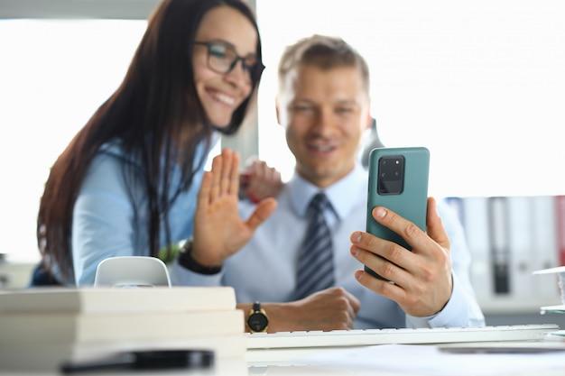Mann und frau lächeln und die begrüßung winkt dem gesprächspartner in einem smartphone zu