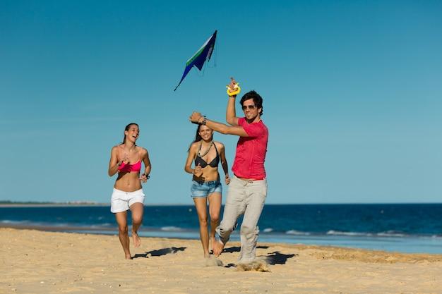 Mann und frau laufen am strand mit drachen