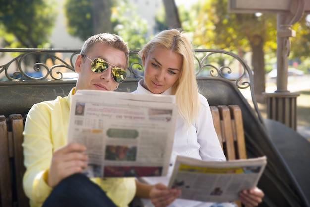 Mann und frau lesen zeitung auf einer bank.