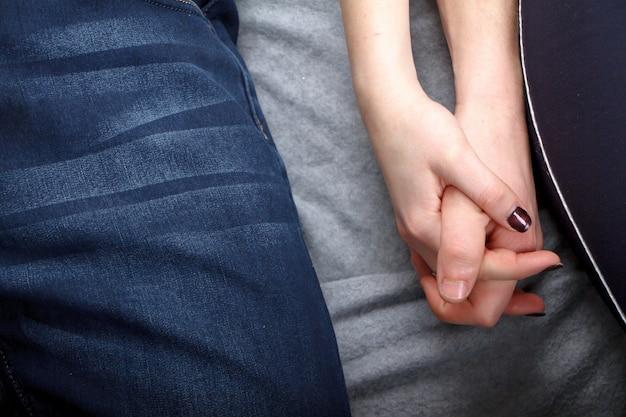 Mann und frau liegen auf dem bett und dem händchenhalten gegen grauen hintergrund
