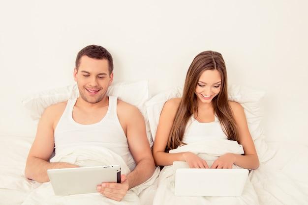 Mann und frau liegen im bett und arbeiten mit laptop und tablet
