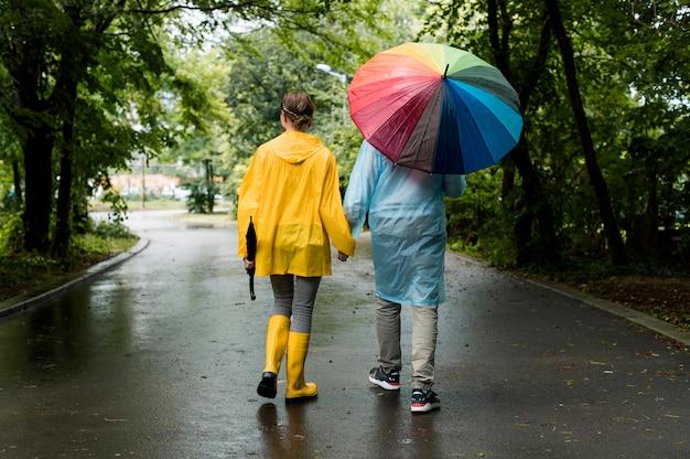 Mann und frau machen einen spaziergang unter dem regen