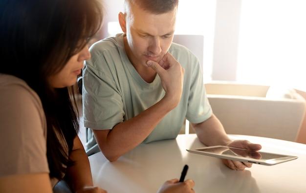 Mann und frau machen einkaufsliste mit tablet