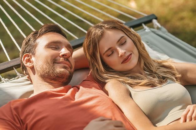 Mann und frau machen mittagsschlaf in der hängematte