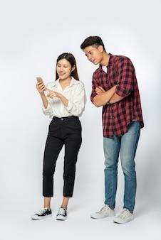 Mann und frau machen sich über ihre smartphones über selfies lustig