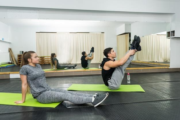 Mann und frau machen übungen, die auf dem boden sitzen
