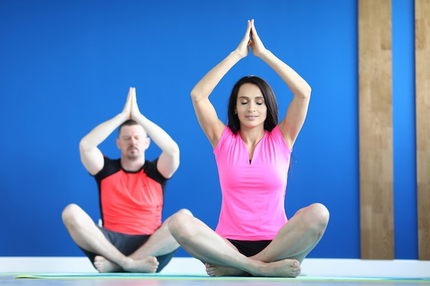 Mann und frau machen yoga im fitnessstudio