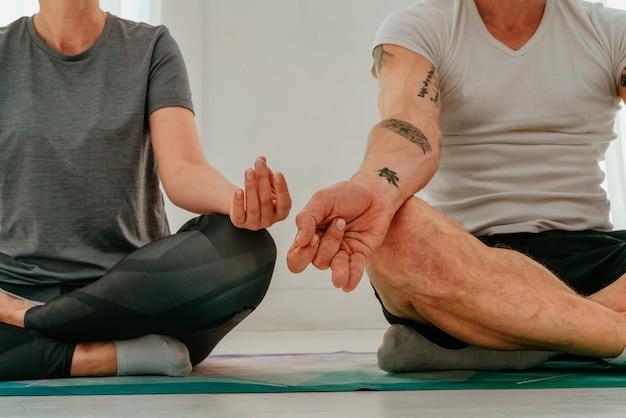 Mann und frau machen zu hause zusammen yogaübungen