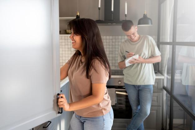 Mann und frau machen zusammen eine einkaufsliste zu hause in der küche