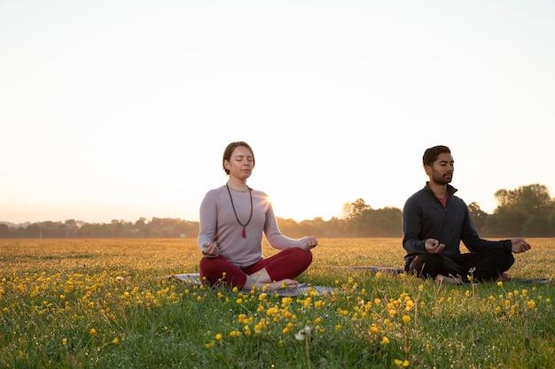 Mann und frau machen zusammen yoga im freien
