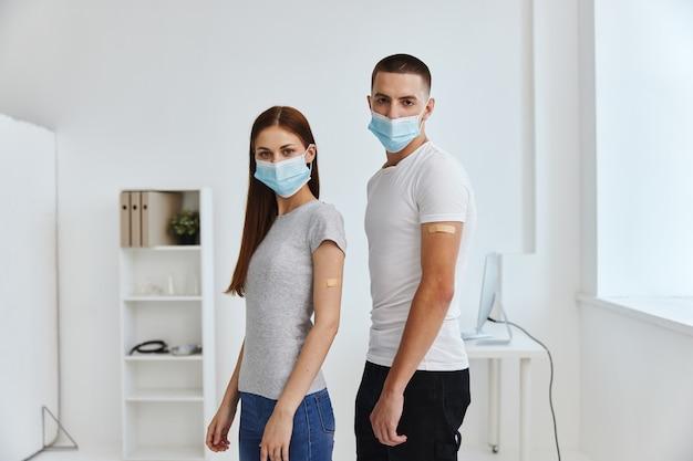 Mann und frau mit geimpften händen tragen medizinische masken immunschutz