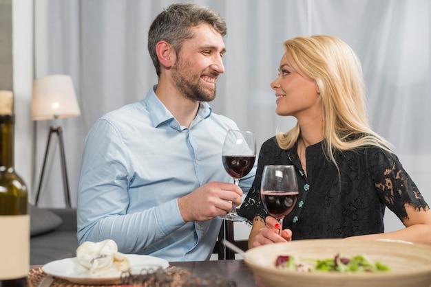 Mann und frau mit gläsern des getränks bei tisch mit schüssel salat