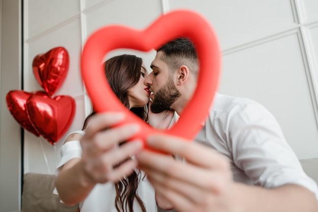 Mann und frau mit herzen formen in die hände, die zu hause mit ballonen durch schauen
