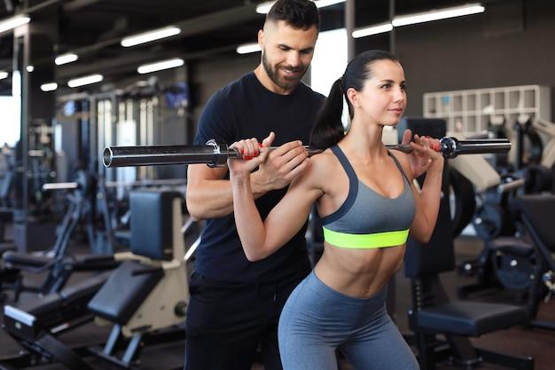 Mann und frau mit langhantel, die muskeln im fitnessstudio beugen.