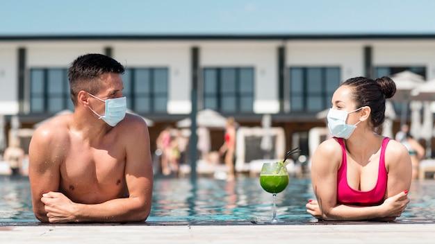 Mann und frau mit maske halten soziale distanz