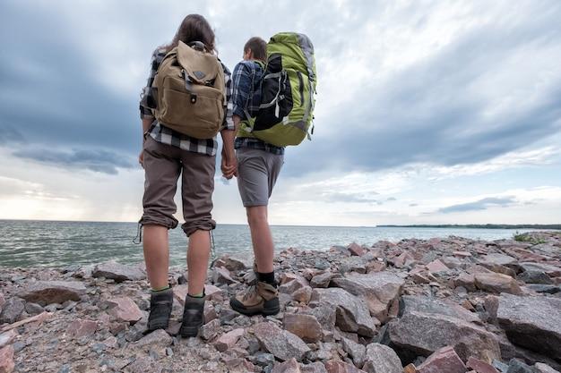 Mann und frau mit rucksäcken in der nähe des meeres