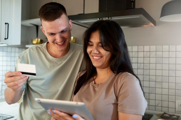 Mann und frau mit tablet für online-shopping mit kreditkarte