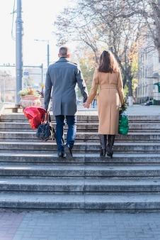Mann und frau mit taschen steigen auf der treppe auf der straße