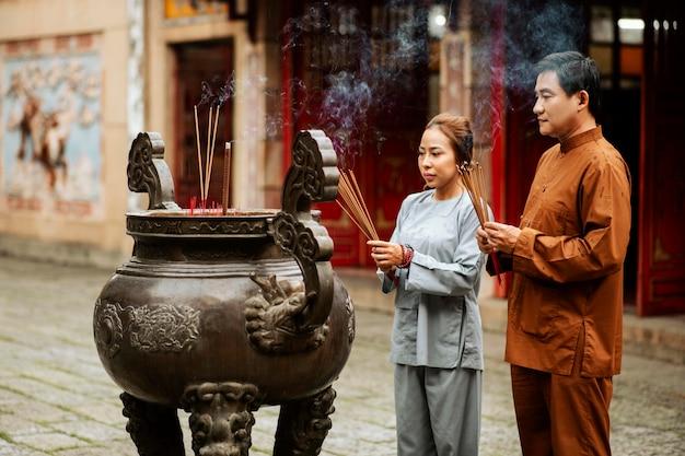 Mann und frau mit weihrauch im tempel