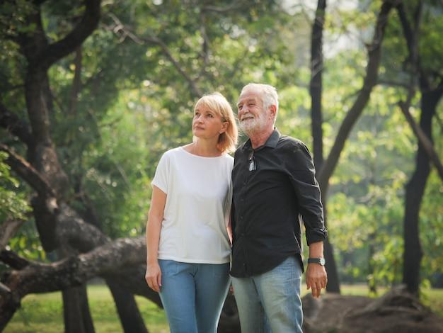 Mann und frau mit zwei glücklichen senioren gehen und sprechen im park