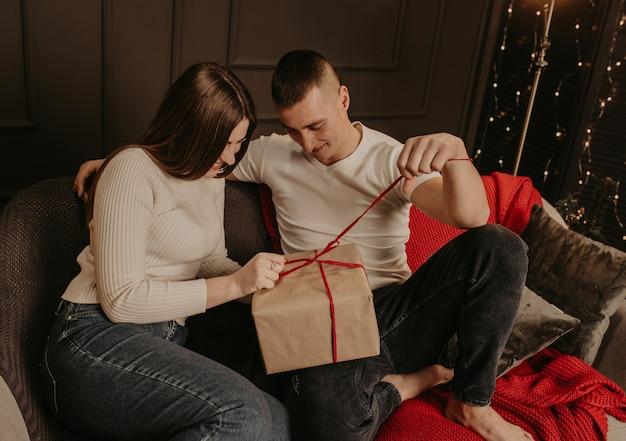 Mann und frau paar in liebe öffnen geschenkboxen lösen einen bogen in der nähe des weihnachtsbaumes
