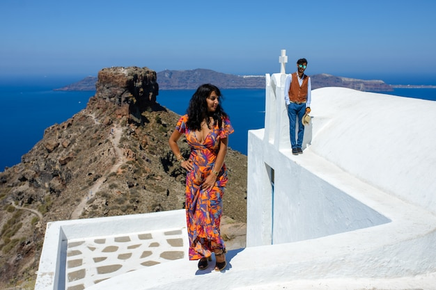 Mann und frau posieren gegen den skaros rock auf santorini island. das dorf imerovigli. er ist ein ethnischer zigeuner. sie ist eine israeliin.