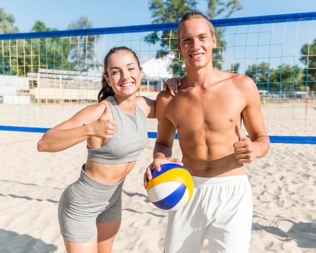 Mann und frau posieren mit daumen hoch, während sie beachvolleyball spielen