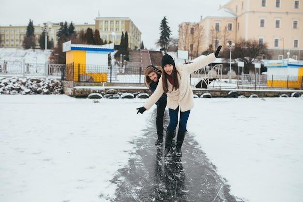 Mann und frau reiten auf dem eis auf einem gefrorenen see